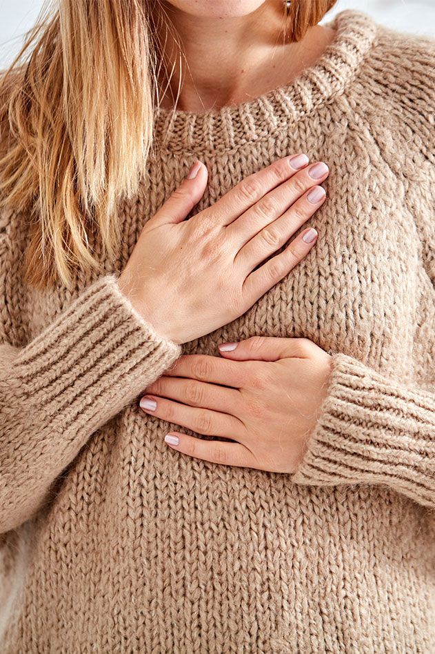 woman holding hands over her chest